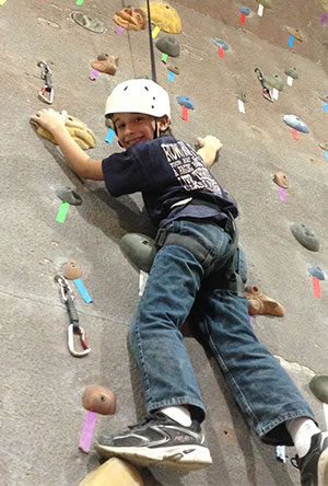 Boy Climbing A Wall After Benefitting From Children Chiropractic Care