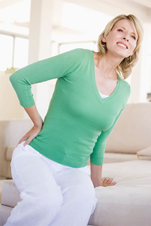 Lady In Green Shirt Suffering From Leg And Lower Back Pain