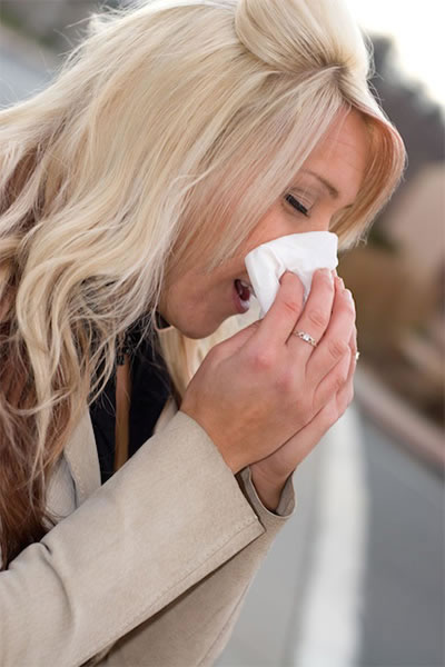 Woman blowing nose, allergies